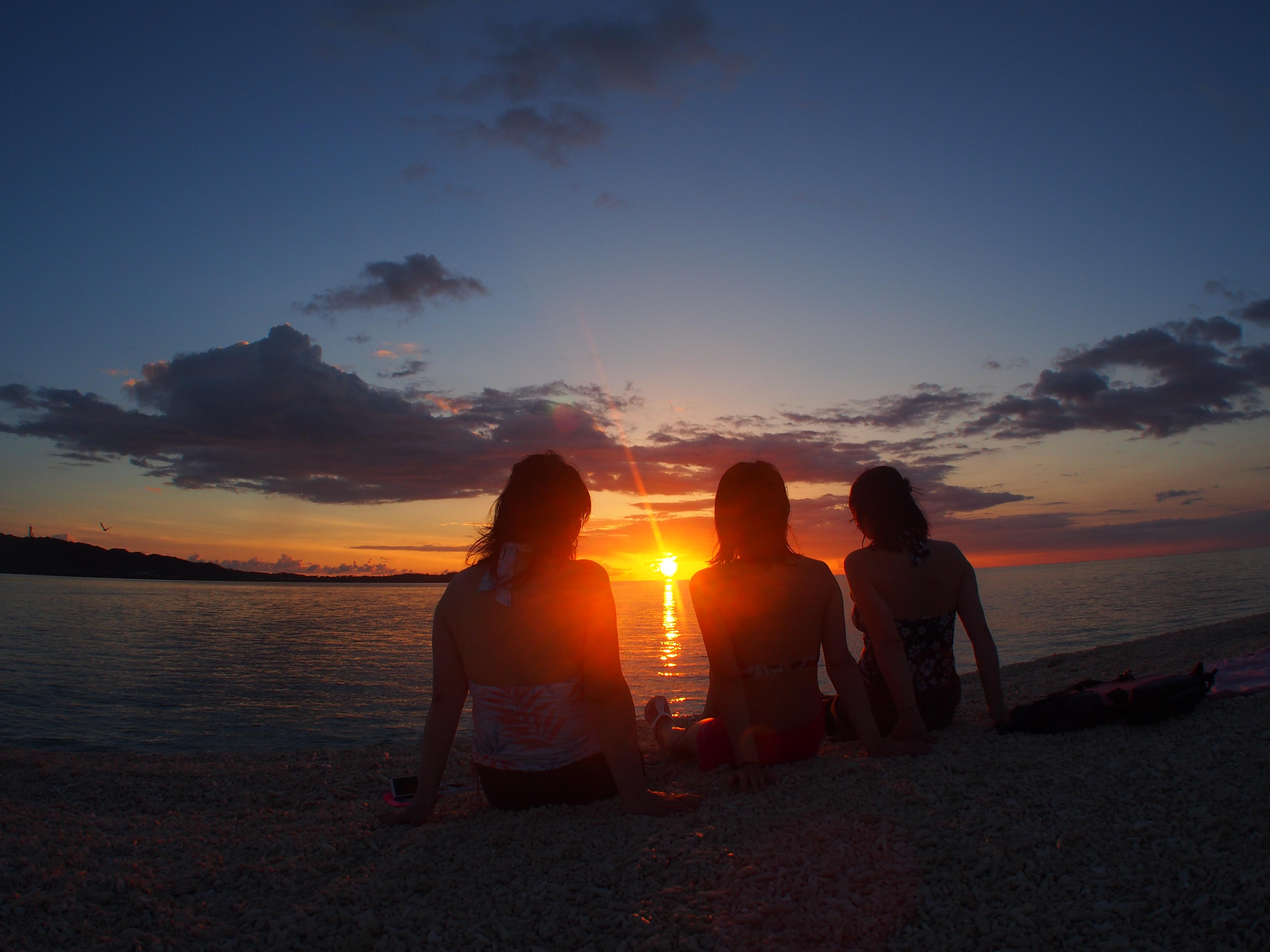 砂浜で並んで沈む夕日を眺める女性達