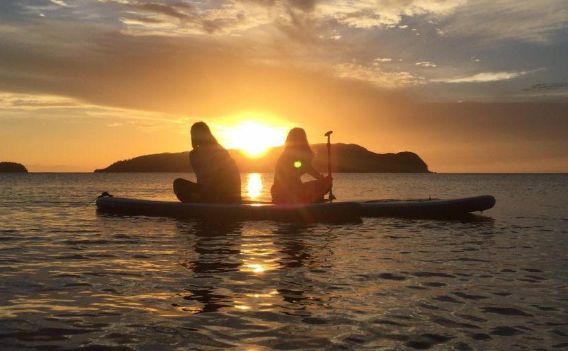 沈む夕日を背にSUPを楽しむ