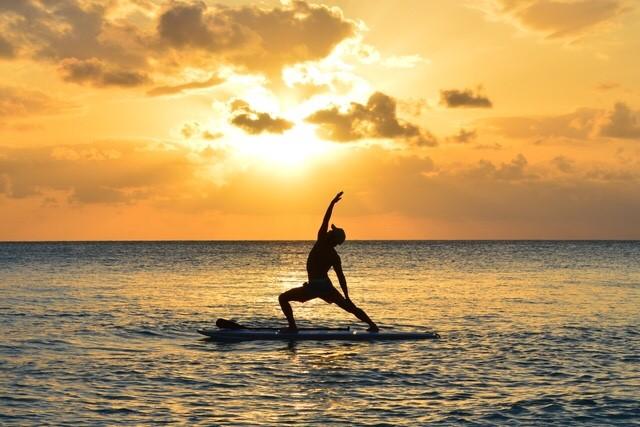 西表島の夕日をバックにSUPでヨガ
