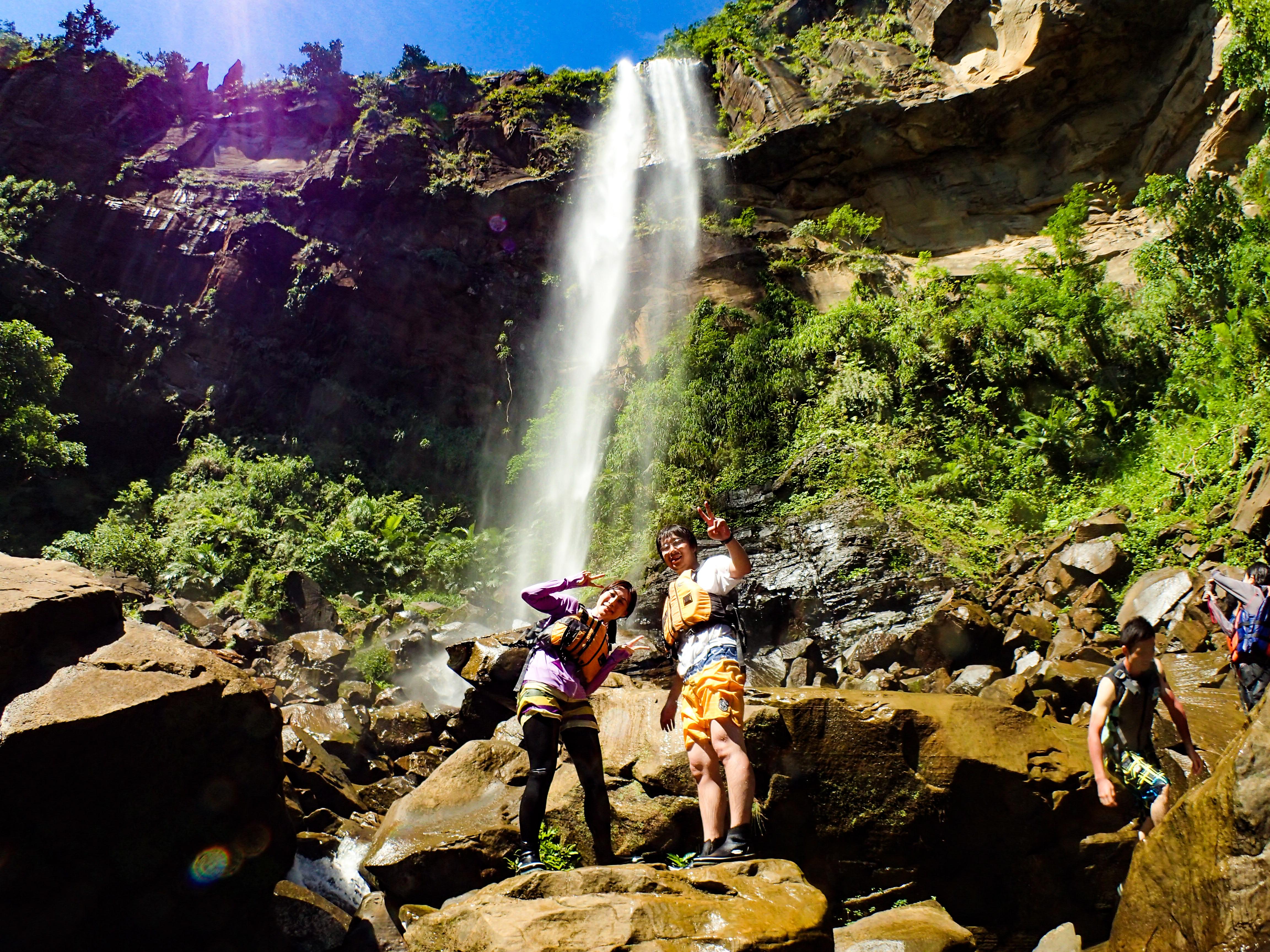 沖縄県下一の落差を持つピナイサーラの滝前で写真撮影