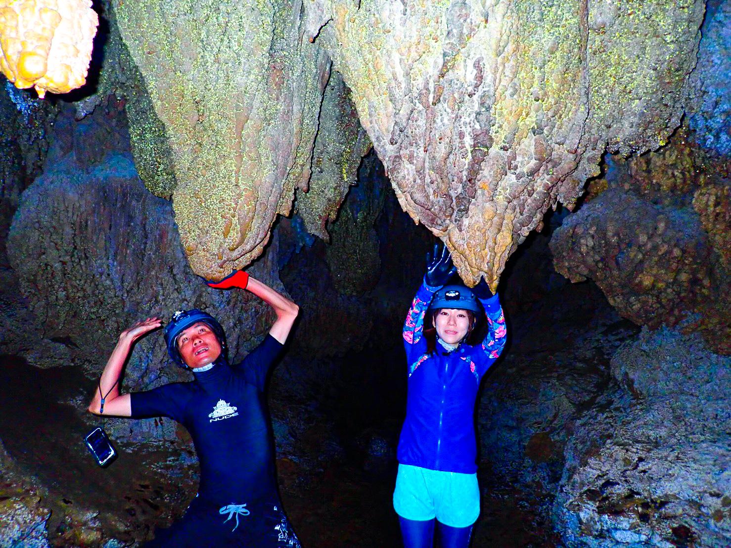 洞窟の中をケイビング中のカップル