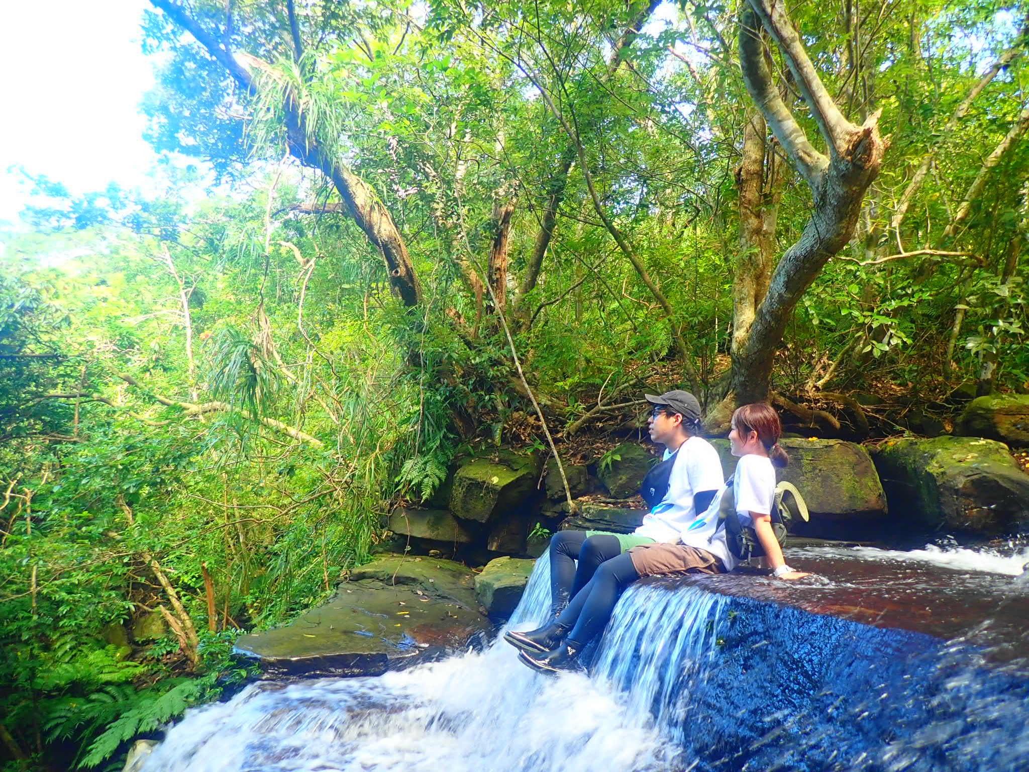 西表島の滝で横になるカップル